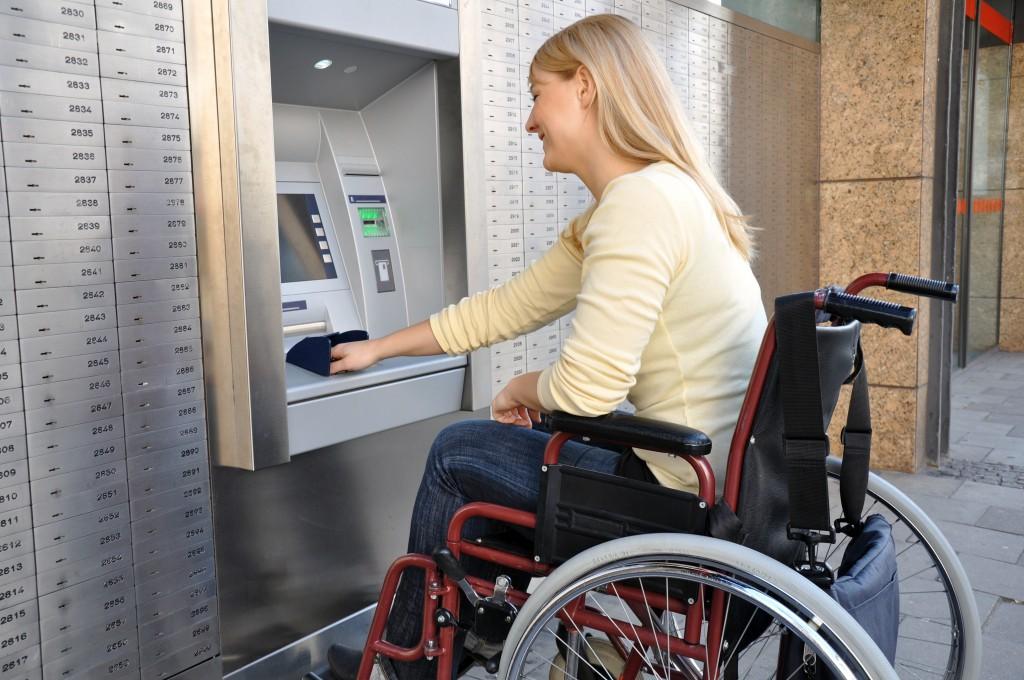 Rollstuhlfahrerin am Geldautomaten